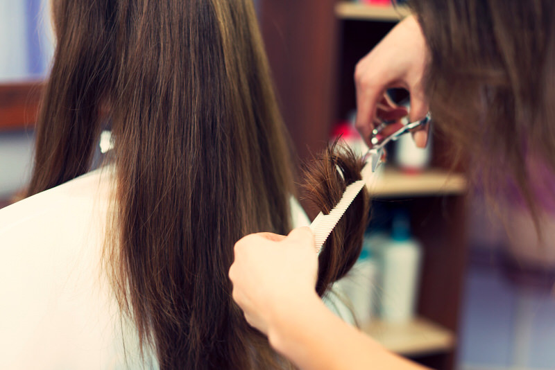 A young pregnant woman is at the salon getting her hair cut.