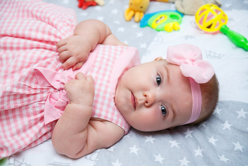 A newborn baby girl is laying on her back, dressed cute in a pink dress and a pink flowery headband.