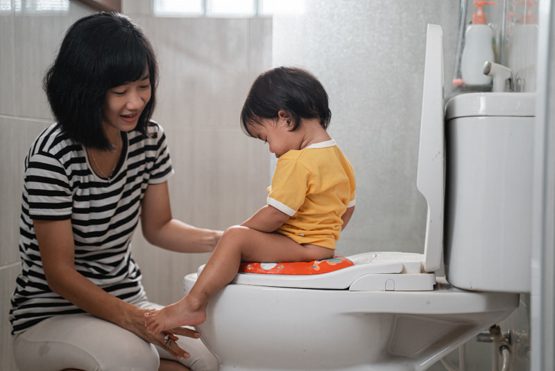 Mom's helping her toddler sit on the potty and poop using a toilet.