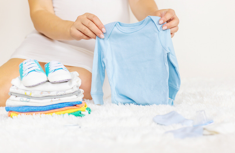 Mom is folding recently washed clothes for her newborn baby.