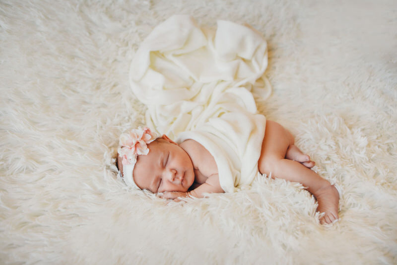 A sleepy newborn is dressed up with a cute white rose headband and a cloth, for her newborn photoshoot.