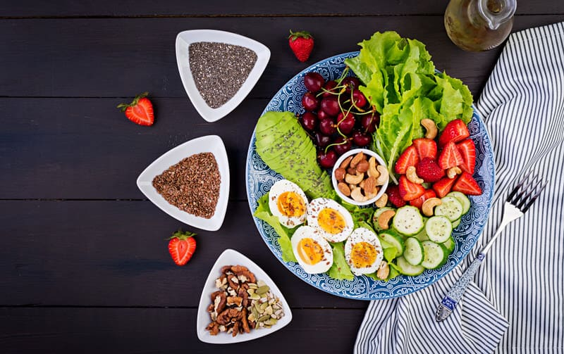 A variety of paleo diet foods, like nuts, eggs, fruits and veggies, are laid out on a table.