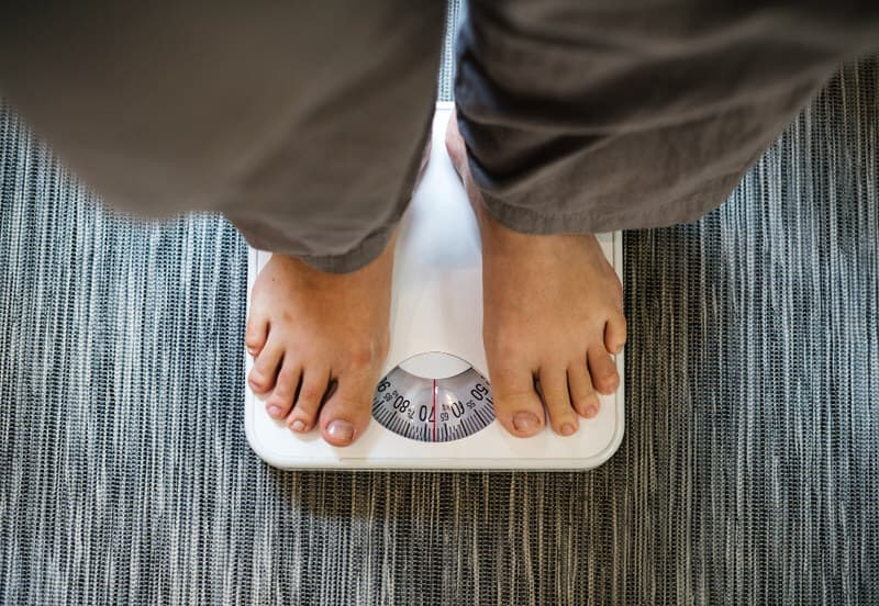 A breastfeeding mom is on the paleo diet to lose weight, and is standing on the weight scale to check her progress.