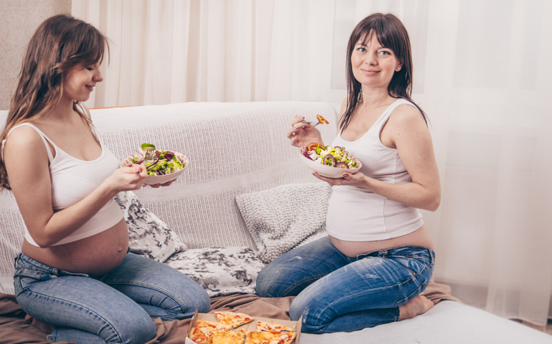 Two girlfriends who are pregnant are enjoying various foods together (like pizza and salad) to fulfill their pregnancy cravings.