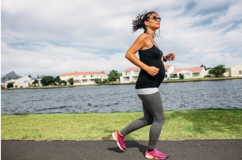 A pregnant woman is speed walking towards the end of her pregnancy to help induce labor.