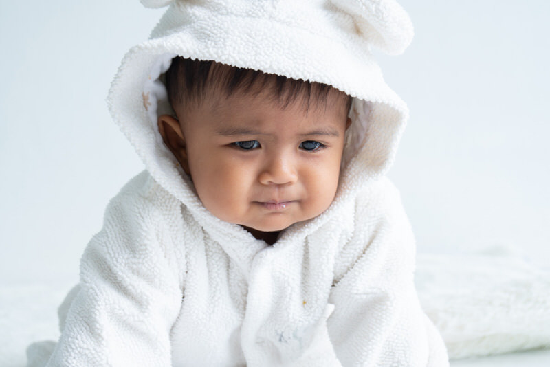 An infant boy is not happy because he's feeling unwell and constipated after eating rice cereal.