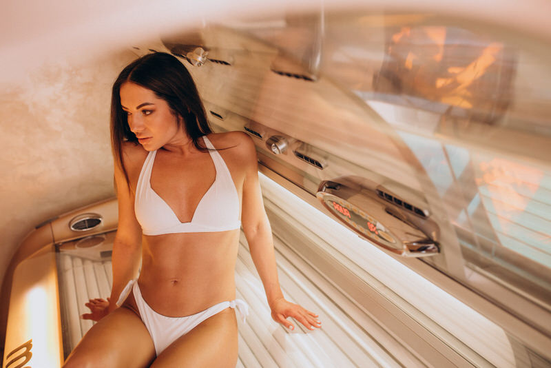A young mom is getting a tan on a tanning bed.