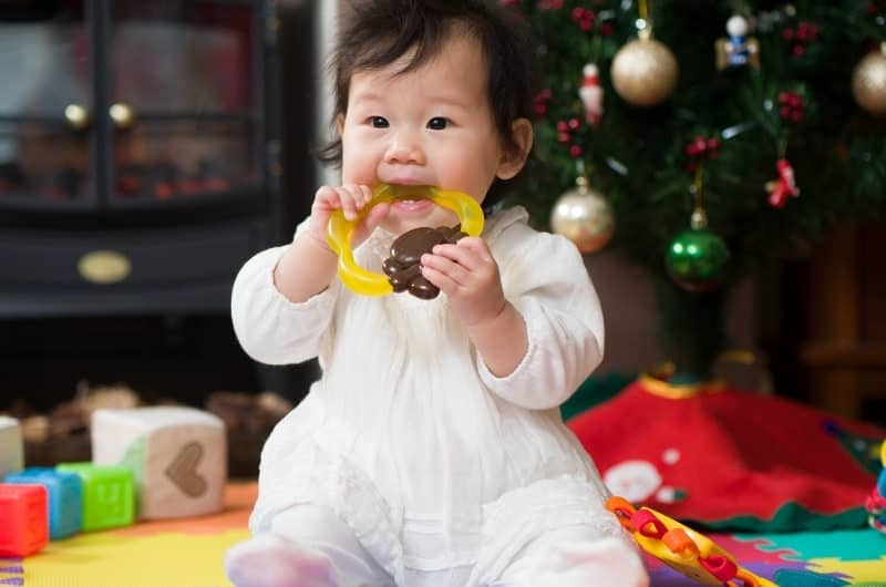 A teething infant girl is playing with a chew toy and biting on it for relief.