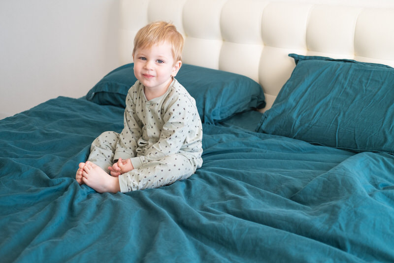 A toddler boy, who woke up quite early in the morning, is sitting on his parent's bed smiling and ready for the day.