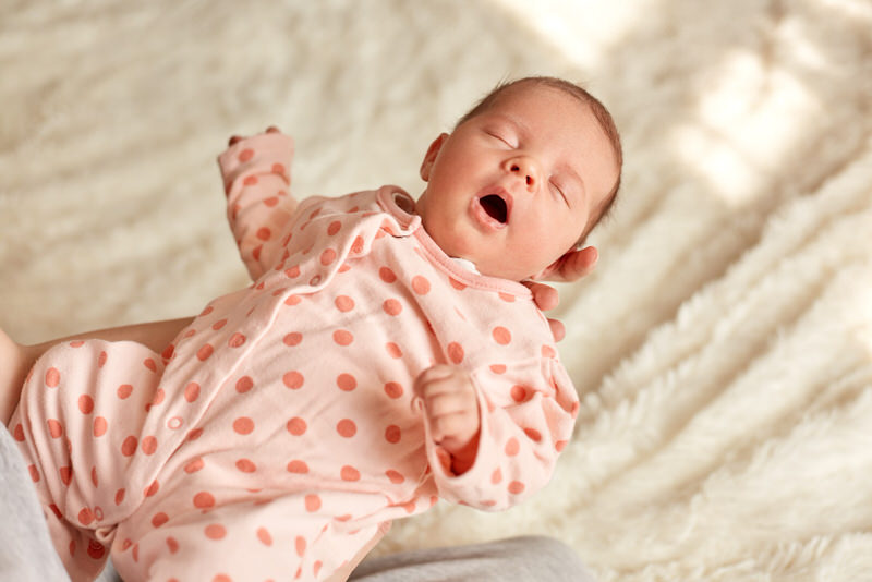An infant girl is sleeping and gasping for air, which is alarming to her parents.