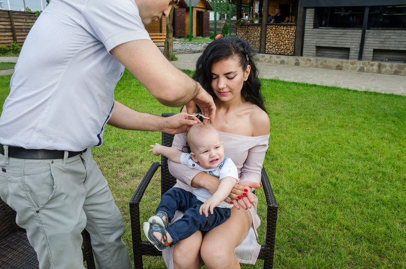 An infant boy is sitting on his moms lap and is about to get his first haircut from his dad.