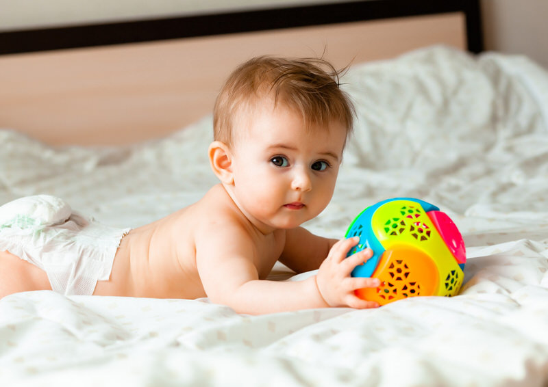 A 6-month baby rolled over on the bed so he could play with his toy ball.