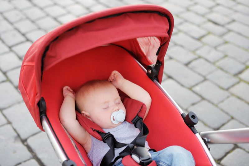 A baby boy is sleeping in a bassinet stroller.