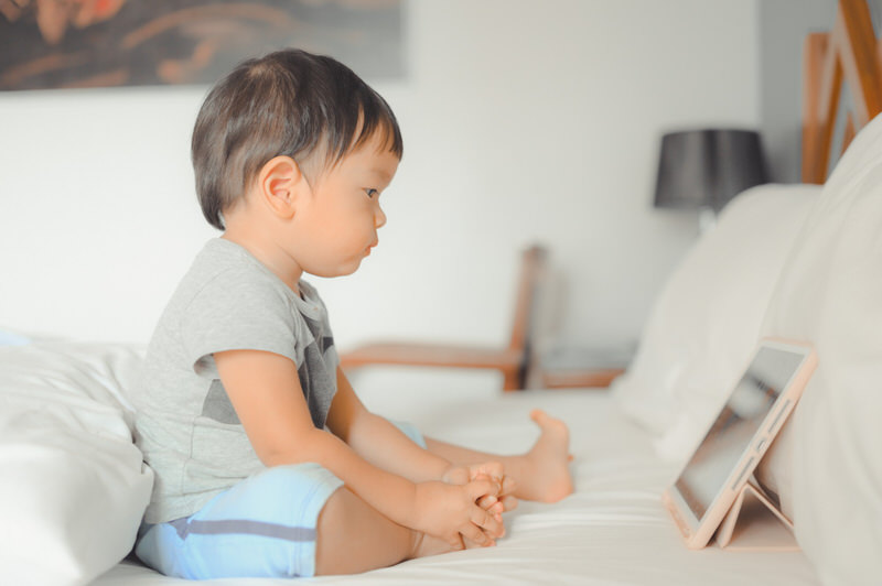 A toddler boy is sitting on the bed, watching a video on his tablet.