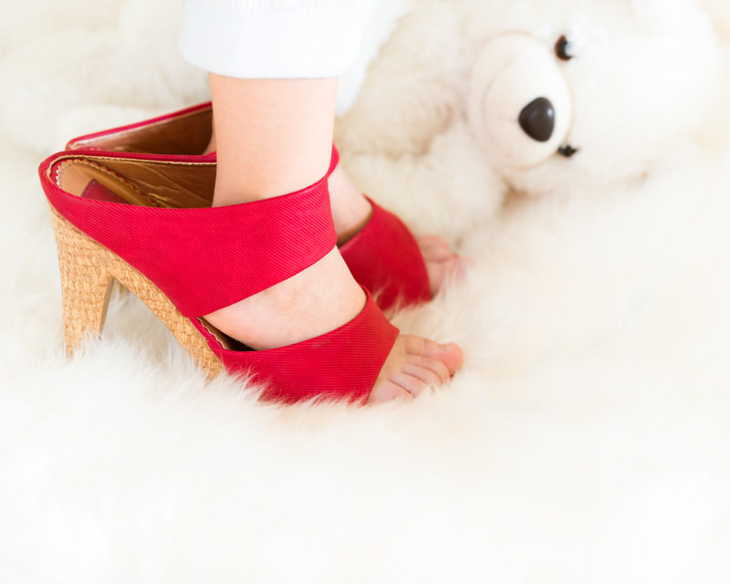 A toddler boy is wearing his moms red heels for fun.