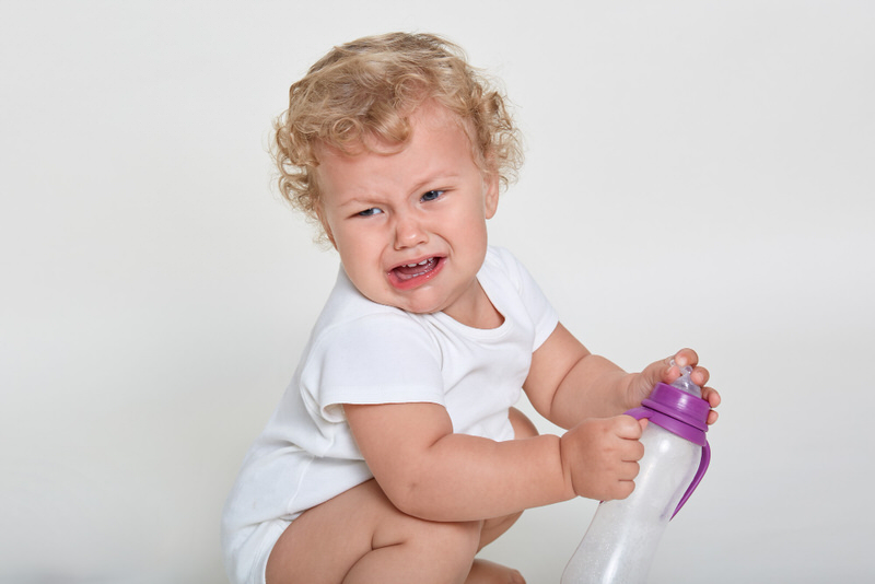 An infant boy is crying and not behaving, and parents are thinking of how to discipline him.