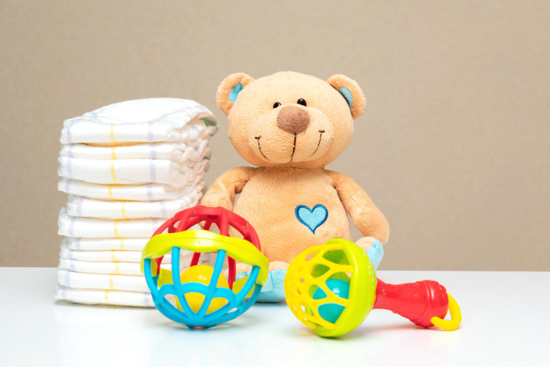 A stack of diapers and soem baby toys are sitting on a changing table.
