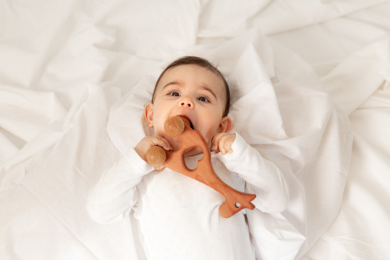 An infant girl is playing with a toy, and doing other things that show she's achieving her milestones.