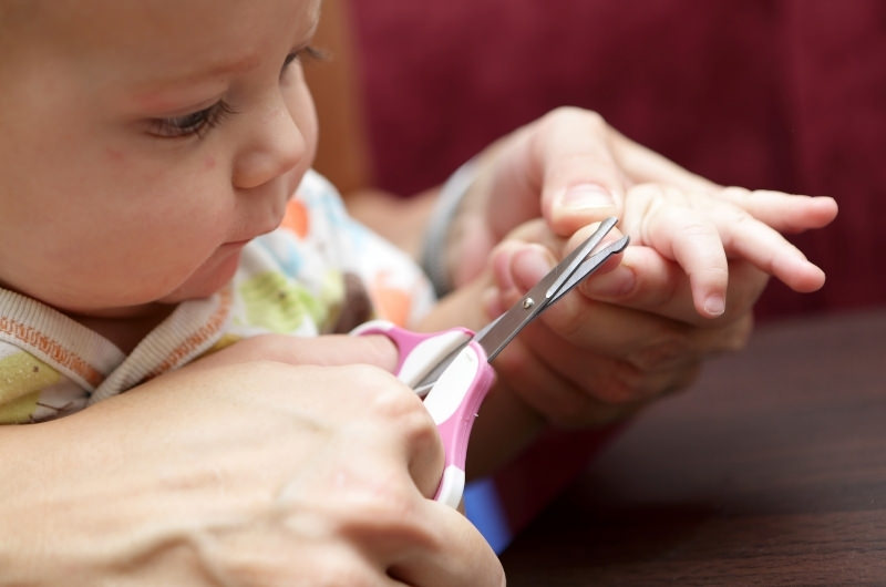 Mom is using a nail scissor to cut her infant son's nails.