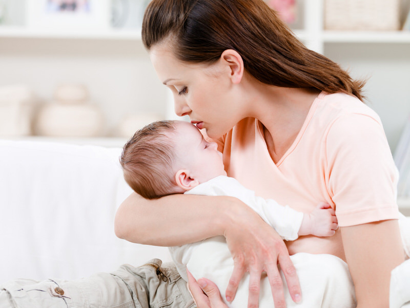 A newborn baby is rubbing his face on his mom's chest as a rooting reflex, maybe because he is hungry or sleepy.
