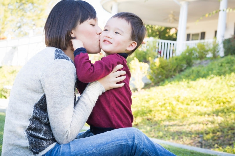 Mom is kissing her toddler son on the cheek after telling him the big news that she is pregnant.