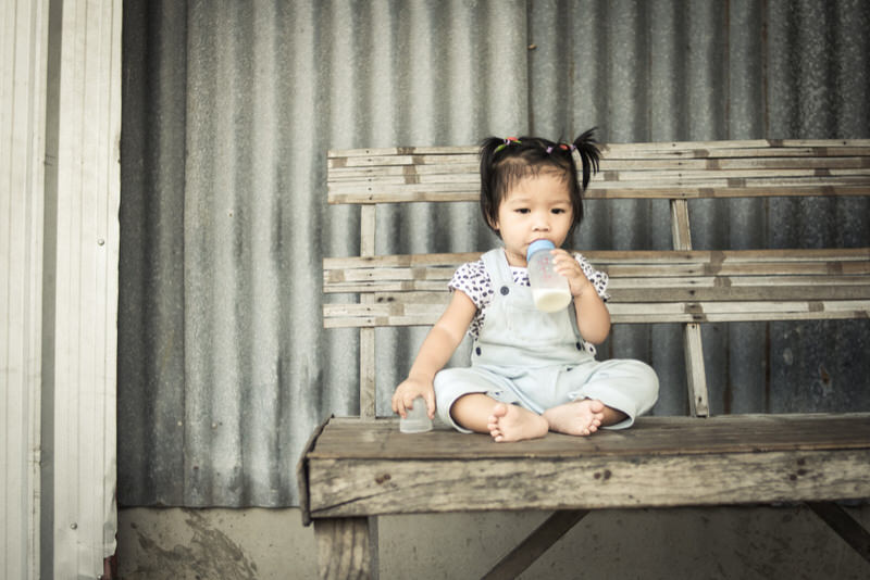 A 1 year old toddler girl is sitting on a bench outside drinking whole milk from a bottle by her self.