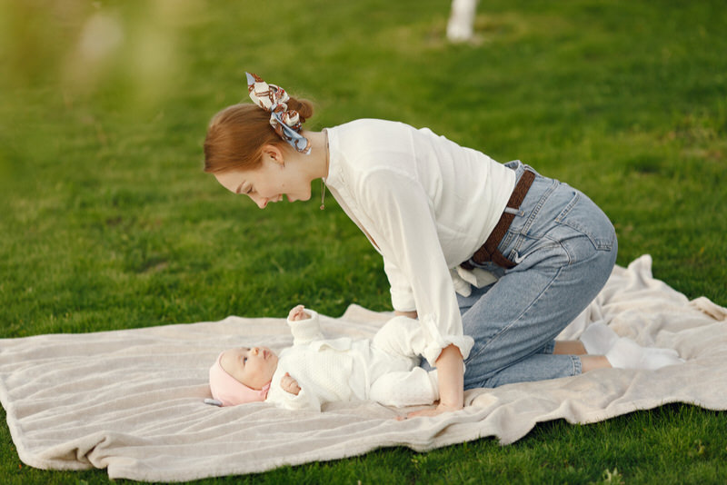 A young mom is with her newborn baby at the park. Baby is laying down on a white blanket, while mom is playing with her.