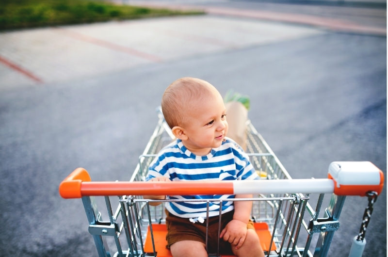 An infant boy is happily sitting in a shopping cart and looking around.