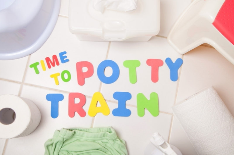 """Letters on the bathroom floor spelling out """"time to potty train"""" with different items that will help a toddler potty train."""