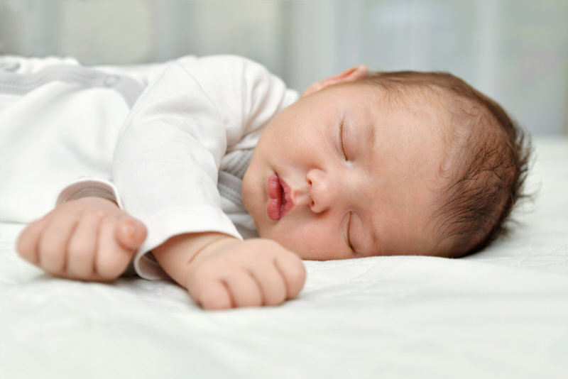 A newborn baby boy is sleeping soundly on his side.
